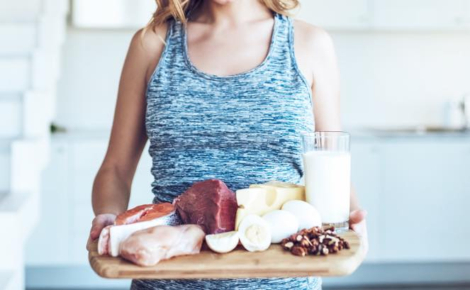 タンパク質が豊富な食材を持つ女性