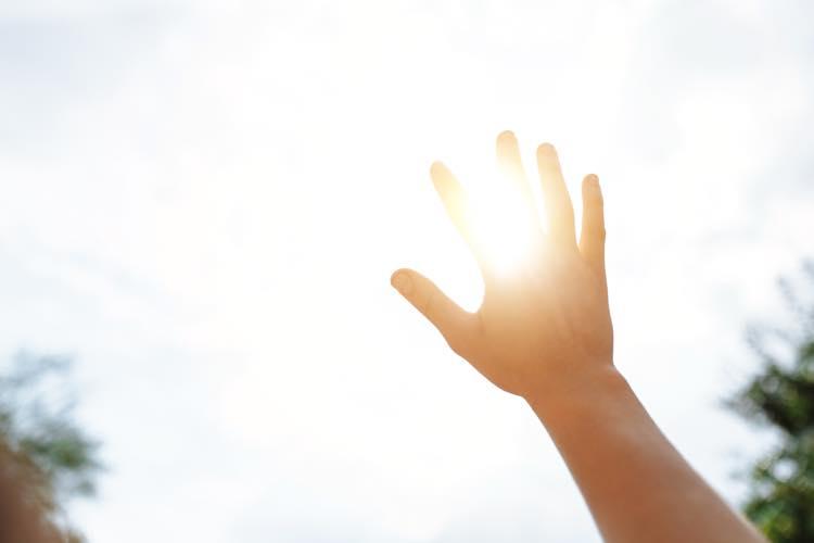 太陽に手をかざす
